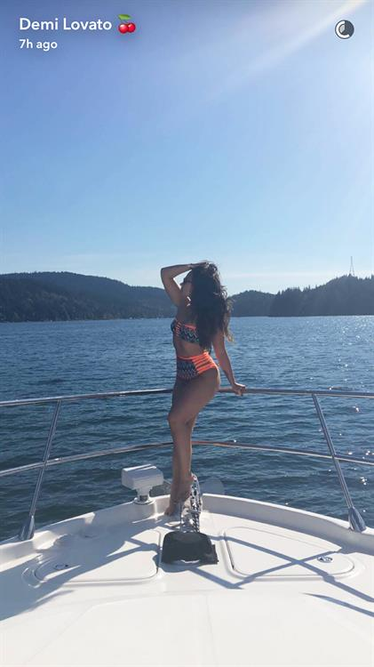 Demi Lovato showcasing her notorious Kardashian effect posturing in front of a boat in a hot neon bikini with a bold pattern and string cutouts.