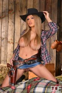 Busty cowgirl, Anastasia, strips off in the barn.